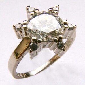 Zásnubní prsten s velkým briliantem a malé brilianty okolo v bílém zlatě.